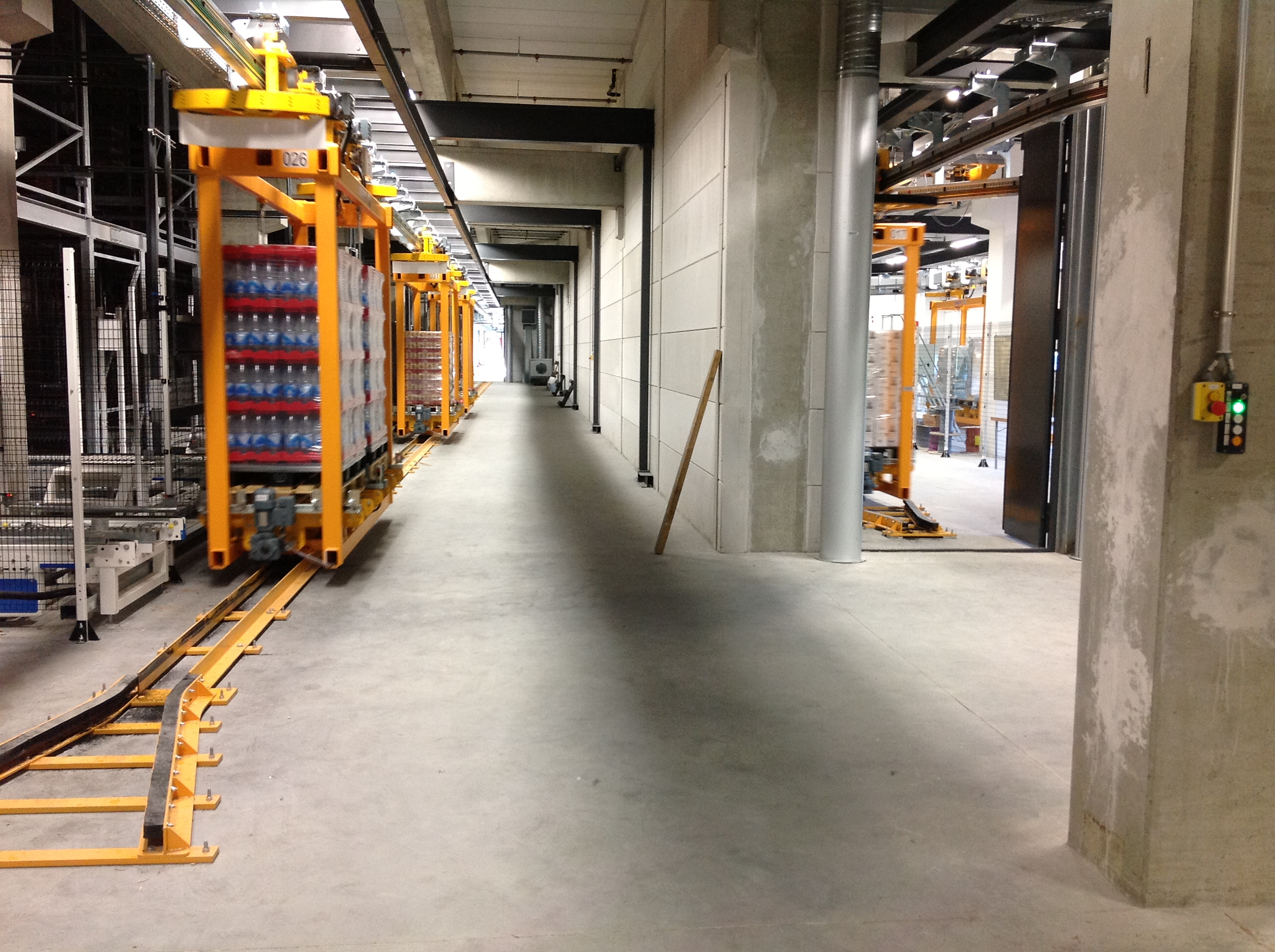 Automated overhead monorail system transfers beverage pallets horizontally in Sweden
